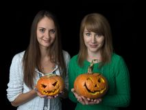 Two charming girls hold on their hands the carved lamp of jack. stock photos