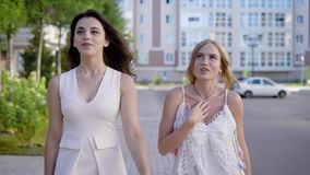 Two charming girls in white stylish dresses talking lively on background of street in summer. Young women having conversation while walking down summer street stock video footage