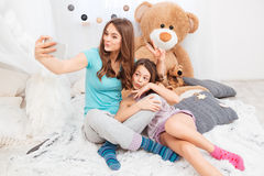 Two charming happy sisters making duck faces and taking selfie Royalty Free Stock Images