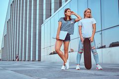 Two charming hipster girls posing with skateboard and laptop on a background of the skyscraper. stock photos