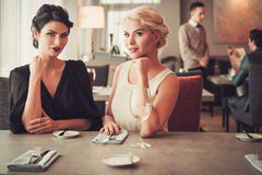Two charming ladies in elegant evening dresses in restaurant Royalty Free Stock Photo