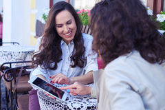 Two charming ladies looking photos at tablet Stock Photos
