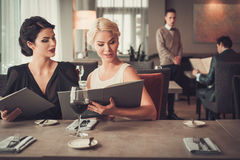 Two charming ladies with menu in restaurant Royalty Free Stock Photography