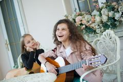 Two charming little girls with guitars royalty free stock photo