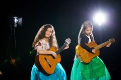 Two charming little girls perform at a solo concert royalty free stock photography