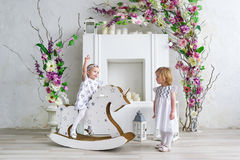 Two charming little girls play in the light room decorated with flowers. Baby girl swinging on a wooden horse Royalty Free Stock Images