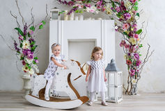 Two charming little girls play in the light room decorated with flowers. Baby girl swinging on a wooden horse Stock Photography