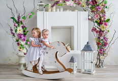 Two charming little girls play in the light room decorated with flowers. Baby girls swinging on a wooden horse Stock Images