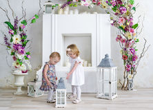 Two charming little girls play in the light room decorated with flowers. Little girls and big candlestick Royalty Free Stock Photos