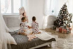 Two charming little girls in their pajamas are having fun jumping on a bed in a sunlit cozy bedroom with New Year`s tree royalty free stock photography