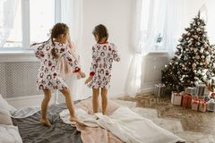 Two charming little girls in their pajamas are having fun jumping on a bed in a sunlit cozy bedroom with New Year`s tree stock image