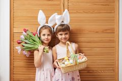 Two charming little sisters in the dresses with white rabbit`s ears on their heads holds flowers and a basket with the stock image