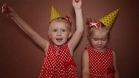 Two charming little sisters twins in holiday caps with sparkling Bengal lights in their hands having fun on a holiday. stock footage