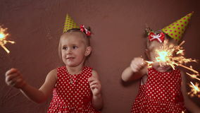 Two charming little sisters twins in holiday caps with sparkling Bengal lights in their hands having fun on a holiday. stock video footage