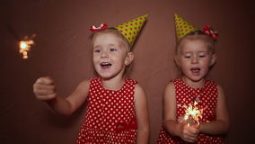 Two charming little sisters twins in holiday caps with sparkling Bengal lights in their hands having fun on a holiday. stock video