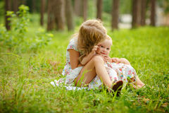 Two charming sisters blonde girl hugging and laughing on the gra stock images