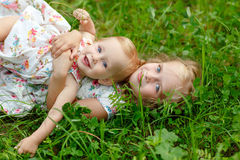 Two charming sisters blonde girl hugging and laughing, lying on royalty free stock image