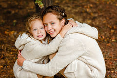 Two charming sisters in the same curly beige knitted sweater embrace on a background of fallen autumn leaves stock photo