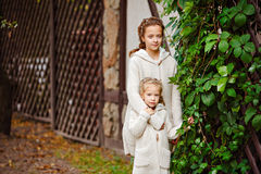 Two charming sisters in the same curly beige knitted sweater embrace on a background of a wooden house and green grapes in autumn stock image
