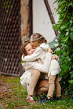Two charming sisters in the same curly beige knitted sweater embracing and kissing on the background of a wooden house and green stock image