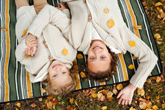 Two charming sisters in the same curly beige knitted sweater lying on a striped rug and a smile on the background of yellow leave royalty free stock photos