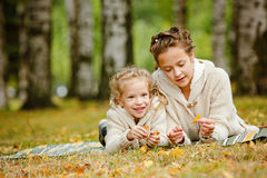 Two charming sisters in the same curly beige knitted sweater lying on a striped rug and smiling, against the backdrop of fallen royalty free stock photography
