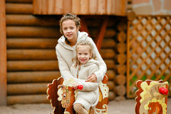 Two charming sisters in the same curly beige knitted sweater smiling and hugging on the background of a wooden house in autumn stock photos