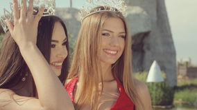 Two charming smiling girls in crowns on their stock footage