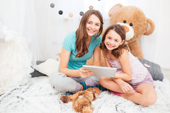 Two charming smiling sisters sitting and using tablet together Stock Image