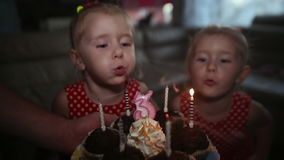 Two charming twin sisters in beautiful red dresses are waiting for a cake with burning candles. They blow candles and. Clap their hands, hugging each other stock video