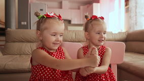 Two charming twin sisters pamper each other, playing with their hands together. Two charming twin sisters pamper each other, playing with their hands together stock video footage