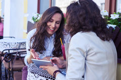 Two charming women discussing photos at tablet Stock Photography