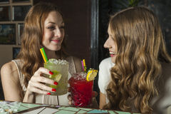 Two charming women drinking cocktails in a bar Royalty Free Stock Photos