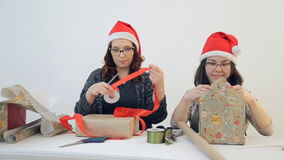 Two charming women pack Christmas gifts. Cute brunette in red New Year cap trimmed with white fur and black square glasses works intently to create festive stock video footage