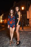 Two charming young brunettes. Posing at night outdoors standing on the road dressed in short overalls stock photos
