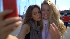 Two charming young women doing selfies on the promenade. Slow Motion. stock video