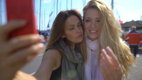 Two charming young women doing selfies on the promenade. Slow Motion. stock footage