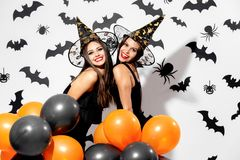 Two charming young women in witches hats hold black and orange balloons on a white background with black bats. Confetti stock photography