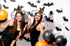Two charming young women in witches hats hold black and orange balloons on a white background with black bats. Confetti stock image