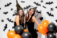 Two charming young women in witches hats hold black and orange balloons on a white background with black bats. Confetti royalty free stock photography