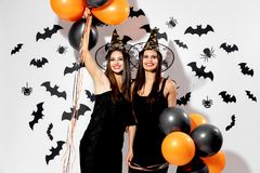 Two charming young women in witches hats hold black and orange balloons on a white background with black bats. Halloween stock image