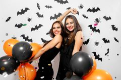 Two charming young women in witches hats smile, have fun with confetti and hold black and orange balloons. Halloween stock photo