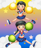 Two cheerdancers dancing with their pom poms. Illustration of the two cheerdancers dancing with their pom poms Royalty Free Stock Images