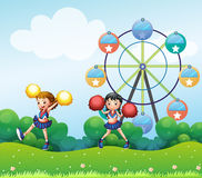 Two cheerers dancing in the hill with a ferris wheel at the back. Illustration of the two cheerers dancing in the hill with a ferris wheel at the back Stock Images