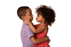 Two cheerful african-american siblings, sister kissing her brother, isolated. On white background royalty free stock photography