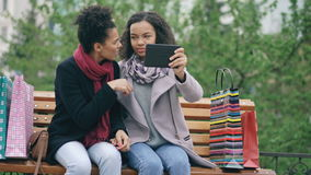 Two cheerful african american women with shopping bags having video call with tablet computer. Young friends sitting on. Bench have online chatting stock video footage