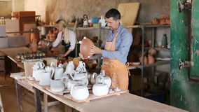 Two cheerful artisans. Having ceramics in hands and standing in workshop stock video