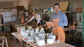 Two cheerful artisans. Having ceramics in hands and standing in workshop stock footage