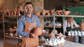 Two cheerful artisans having ceramics in hands. And standing in workshop stock footage