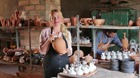 Two cheerful artisans having ceramics in hands. And standing in workshop stock video footage